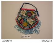 Bag, brown velvet, heavily embroidered all over with multi coloured stylized floral design, decorative flaps attached to front and back, edges bound red wool, pale blue bead fringe to lower edges, top opening bound pink ribbon, blue ribbon handle strap,