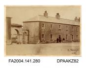 Photograph, the main entrance and the Officers Quarters at Cahir Barracks with men grouped around the doorway, taken by R Vervega, 1869vol 1, page 35
