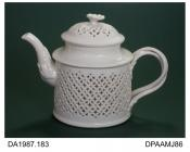 Teapot, creamware, double-walled, drum shape, the outer wall pierced with a reticulated pattern in the manner of late 18th century examples made at Leeds, double intertwined handle with flower terminals, impressed factory mark on base, Royal Creamware,
