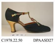 Shoes, pair, women's, evening shoes, black crepe chine edged and trimmed gold kid, complex cross-over T-straps trimmed with green and red dyed lizard skin roundels ending in imitation tassels, red cut paste buttons, button missing on left shoe, cut away
