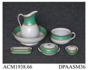 Toilet set, consisting of ewer and basin, sponge and soap dishes, toothbrush box and chamber pot, white earthenware, decorated with wide green bands and printed borders painted in yellow enamel and gilt; red painted pattern number D2038 on each part, an