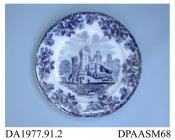 Dinner plate, or side plate, white earthenware, decorated with one of a group of flow blue printed designs showing a ruined lakeside castle within a border of oak leaves and acorns; back, impressed crown, printed factory mark in green and printed regist