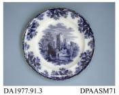 Dinner plate, white earthenware, decorated with one of a group of flow blue printed designs showing a ruined lakeside castle within a border of oak leaves and acorns; back, impressed crown, printed factory mark in green and printed registered design mar