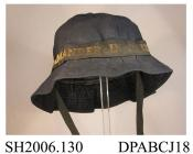 Hat, WREN's uniform, soft navy blue twilled cotton, soft crown in six sections with covered button to centre, narrow brim with stiffening and topstitched detail, black silk cap tally with Commander in Chief woven in gilt thread, black cotton tape ties,