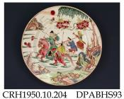 Plate, hard paste porcelain, decorated in famille rose colours with a warrior on horseback and attendant carrying a sword, box and writing scroll, they are crossing marshy ground; not marked, made in Jingdezhen, Jiangxi Province, with decoration possibl