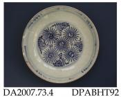 Saucer dish, hard paste porcelain, thickly potted, with crazed glaze, decorated with underglaze blue painted stylised flowers in well, accretions to footring; not marked, possibly Chinese provincial or other east-Asian country, c1700-1800