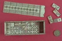 Dominoes, bone box with wooden base and small compartment at one end, with sliding lid, containing a double nine set of small bone dominoes, the lid is perforated to form a cribbage board, decorated with carved and coloured circular pattern, 19th centur