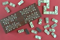 Dominoes, wooden box with hinged lid inlaid with a mother of pearl floral design, and a metal handle and lock, containing a double nine set of bone dominoes, the dominoes are white on top of black bases and are held together by a either a central brass