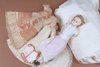 Doll, wax over composition head, with blue glass eyes and hand painted features, blonde hair plaited over forehead, drop earring below earlobe, stuffed fabric body with wax over composition limbs, painted black boots, c1870s the doll is wearing; drawers