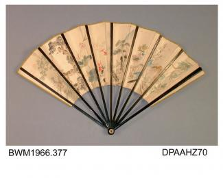 Fan, paper leaf painted with oriental scene of exotic birds, monkeys, goldfish and two figures, one of whom is wearing a white fur jacket, plain black lacquered sticks and guards with etched detail, reverse cream with gold flecking, narrow outer border