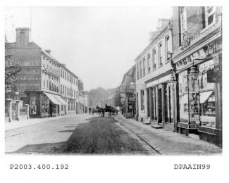 Black and white photographic enlargement of postcard showing view looking east along London Street, Basingstoke, to left is shop and premises of Harry Edmund Powell, pianoforte, organ, harmonium and music warehouse, with Red Lion Hotel beyond, on right