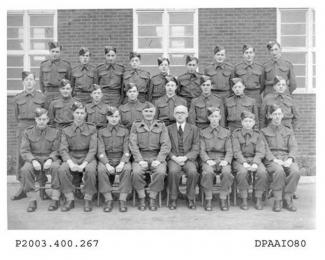 Sepia photograph showing group portrait of Queen Mary's Grammar School, Basingstoke Army Cadet Corp with 22 boys and men standing or seated in army uniform including Sergeants and Corporals, one other man with glasses wearing a suit is seated in front r