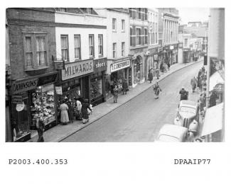 Black and white photograph showing oblique view from elevated point looking south west along south side of Winchester Street Basingstoke, from number 7 upwards, from left, number 7 Johnson Brothers, dyers, number 9 Lavalls Ltd, confectioners - with sign
