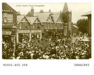 Sepia postcard showing view looking north east from Winton Square, Basingstoke at top of Sarum Hill on the 20th July 1908, a large crowd of men, women and children are surrounding three cars, in the back of the central car is standing, with long white b
