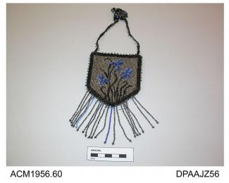 Bag, small, shield shaped, slightly stiffened, front of black material closely beaded with design of irises in blue and black on silver ground, outer border of black beading, edges trimmed silver and black beads, base trimmed long beaded fringe in silve