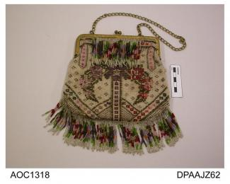 Bag, gilt frame with twist knob closure and chain handle, cream net beaded with stylized flower arrangement in shades of purple, red and olive green on ivory opalescent ground, lower edge trimmed long multi coloured bead fringe, matching fringe attached