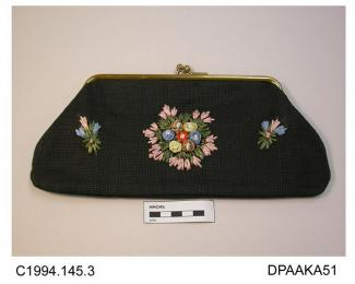 Bag, clutch or pochette type, crisp black fabric, possibly hessian, front decorated with colourful raffia flowers, unlined, on plain gilt frame with cross over snap closure, approximate width 285mm, approximate depth 125mm, c1947