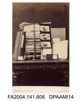 Photograph, a table laden with some of the photographs, briefs, documents and letters held by Mr Henry Hawkins QC during the Tichborne v Lushington trial, taken by The London Stereoscopic and Photographic Companyvol 1, page 74