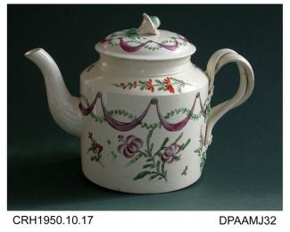 Teapot, creamware, drum shape, double intertwined strap handle with flower terminals, fluted curved spout, flower knop on lid, decorated with swags and lilies in green, iron red and purple enamels, not marked, possibly made in Leeds, West Yorkshire, c17