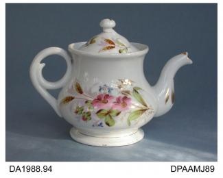 Teapot, hard paste porcelain, pear shape with coiled handle, decorated with painted pink flowers, barley and bright gilding, not marked, possibly made in one of the European countries formerly constituting Bohemia, c1900-1910