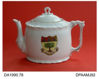 Teapot, hard paste porcelain, oval shape, with shell moulding to rim and foot, rococo handle, crest of the town of Aldershot, Hampshire, enamelled over transfer print, not marked, made in one of the European countries formerly constituting Bohemia, c189
