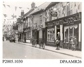 Photograph, black and white, showing decorated shops, in honour of King George V Silver Jubilee, Lower Church Street, Basingstoke, Hampshire. 1935