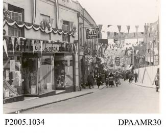 Photograph, black and white, showing decorated shops, in honour of King George V Silver Jubilee, Upper Church Street, Basingstoke, Hampshire. 1935