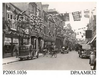 Photograph, black and white, showing decorated shops, in honour of King George V Silver Jubilee, London Street, Basingstoke, Hampshire. 1935
