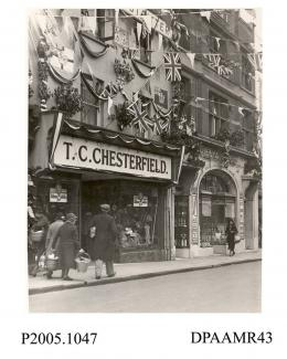 Photograph, black and white, showing decorated shops, in honour of King George V Silver Jubilee, Winchester Street, Basingstoke, Hampshire. 1935