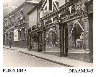 Photograph, black and white, showing decorated shops, in honour of King George V Silver Jubilee, Wote Street, Basingstoke, Hampshire. 1935