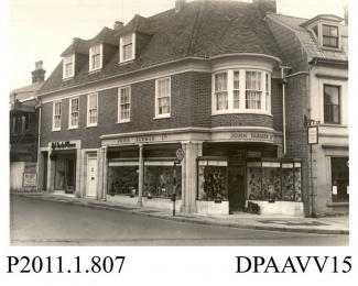 Photograph, black and white, showing the shop front of John Farmer Limited, shoe mfr, corner of Market Street and High Street, Alton, Hampshire