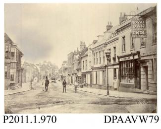 Photograph, black and white, showing The Royal Oak, innkeeper, and the shop fronts of C T Knight and Daysh, High Street, Alton, Hampshire, 1855 - 1870