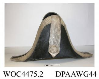 Cocked hat, men's, high cocked black fur felt, rigid, sharply cocked at front and back, edges trimmed with wide band of silver braid, front also trimmed with wide vertical band of silver braid and a large domed button covered with basket weave silver th