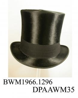 Top hat, men's, part of coachman's livery uniform, black silk plush, high slightly waisted crown, broad black wool frieze hatband, narrow brim with curled sides and edged black ribbed silk ribbon, underside of brim covered with black woollen fabric, dee
