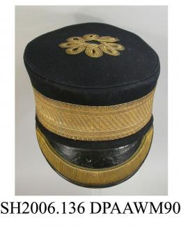 Cap, peaked cap, men's, very dark navy wool, soft flat top to crown trimmed with scrolled motif in gold braid, crown edged piped with matching fabric, stiffened hatband trimmed with broad band of gold ribbon, front peak covered black patent leather trim