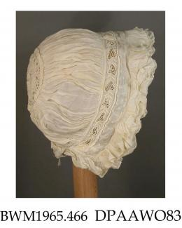 Bonnet, cap, infant's, coif style, fine white linen, headpiece has three drawstrings with whitework dots and ayrshire work leaves with various needle fillings, three frills round face, one frill at nape, puffed caul gathered onto headpiece and onto 60mm