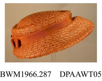 Hat, women's, light tan synthetic straw, low crown trimmed tan petersham band with flat bow at rear, shaped medium brim, inner band of narrow brown petersham, unlined, round black elastic to hold on head, approximate length 240mm, approximate height 100