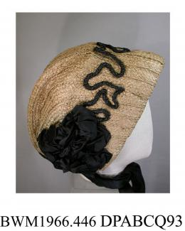 Bonnet, women's, natural split straw over cream net, softly pleated to shape at the nape, trimmed with black straw cord in vermicelli pattern over the front, decorated with large complex black satin ribbon rosettes over each cheek, with wide black satin