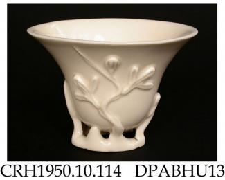 Libation cup, one of two similar, hard paste blanc de chine porcelain, with relief-moulded decoration springing from the openwork foot; not marked, made in Dehua, Fujian Province, China, c1680-1700 the overall flattened conical shape derives from exampl