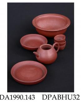 Toy tea set, red stoneware, consisting of a teapot (lid missing), three tea bowls, a saucer dish, a flat dish or tray and a large bowl; not marked, made in Yixing, Jiangsu Province, China, late 19th century to c1950