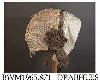 Bonnet, child's, turnback brim of fine white cotton embroidered with large dots and a scalloped edge, trimmed twisted band and large rosettes of bronze satin ribbon, caul made of pintucked organdie with 15mm dark cream valenciennes lace insertions at 35