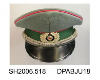 Cap, men's, military, East German officer's cap, grey green wool piped cherry coloured cord, hatband covered green wool, cap badge, pale grey cord trim above front peak, peak of moulded plastic, wreath badge with red centre, grey caplines, shiny black a