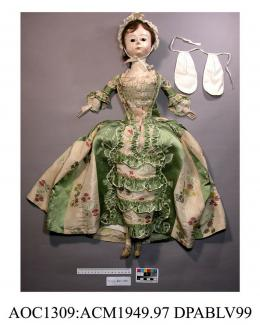 Doll, fashion doll or Pandora, made of wood, with jointed limbs, painted face and body and glass eyes, with real hair,1750-1770 the doll is wearing a sack back dress of green and cream striped silk brocade over a stomacher. There is a full set of underg