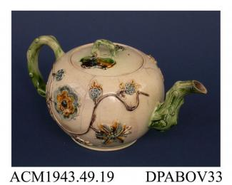 Teapot, earthenware, globular shape with crabstock spout and handle and applied Tudor rose and other flower sprigs linked by a trailed clay stem, decorated underglaze with slate-blue, green and brown oxides; not marked, attributed to Thomas Whieldon and