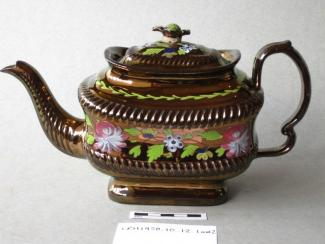 Teapot red earthenware, oblong shape, full copper lustre with a central frieze of enamelled leaves and flowers, not marked, probably made in Staffordshire, c1820-1830